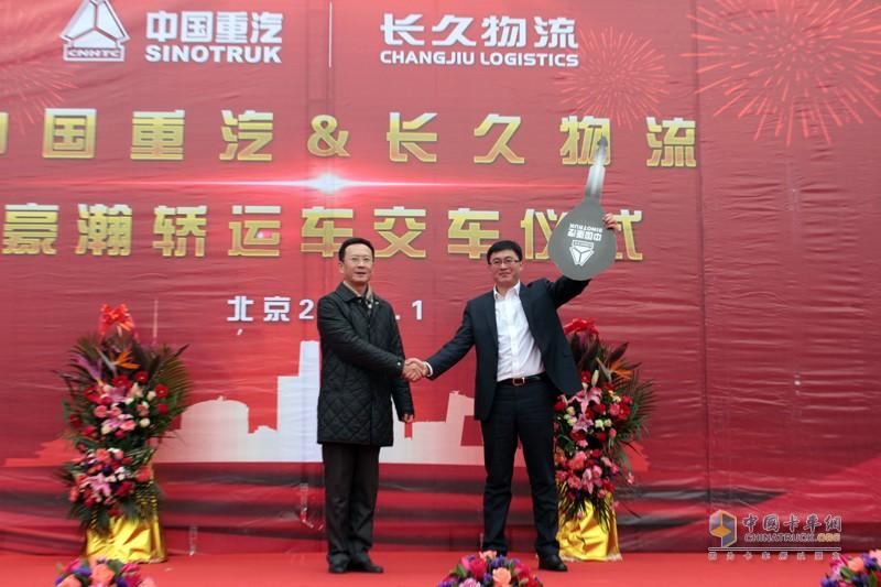 中国重汽销售部北京分公司总经理牟磊向长久物流合作发展部部长李涛交付车钥匙