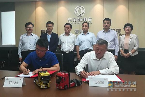 东风汽车贸易有限公司副总经理邱波与鸿运达物流总经理黄世安签约