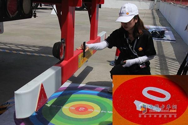 工作人员通过红点测量倒车停车得分,席宝昌师傅不偏不倚刚好停在了10分的范围内