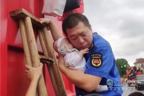 救援队员把仅仅一个多月的婴儿紧紧抱在怀中