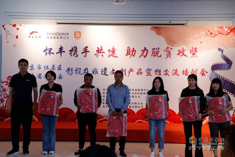 福田戴姆勒汽车副总经理、华北分公司总经理刘刚向重卡司机家属代表捐赠学习文具