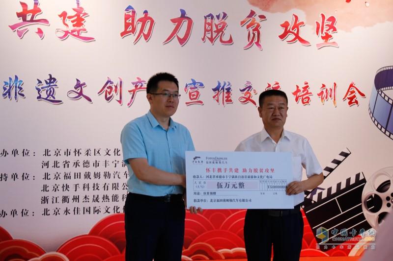 福田戴姆勒汽车党委副书记、纪委书记李汉志向丰宁旅游和文化广电局捐赠扶贫款
