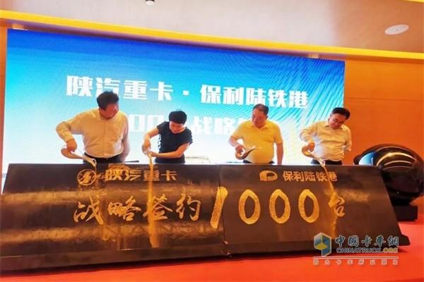 陕重汽副总经理兼销售公司总经理周银朝与新疆保利陆铁港集团董事长叶浩签署1000辆购车协议
