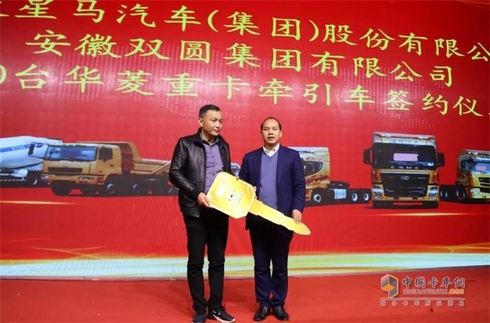 华菱星马集团公司总经理助理葛晓生(右)将象征财富的金钥匙交付到了胡传峰(左)手中