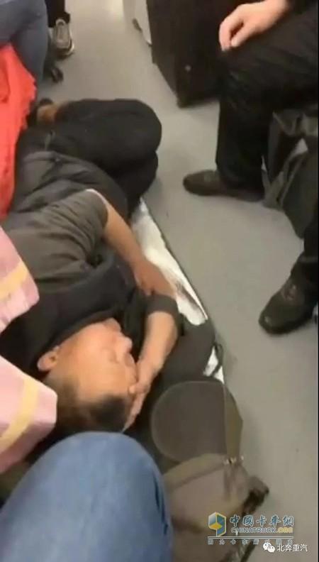 图为送车公司将车辆送达天津后,买不到返程车票,睡在车厢过道上