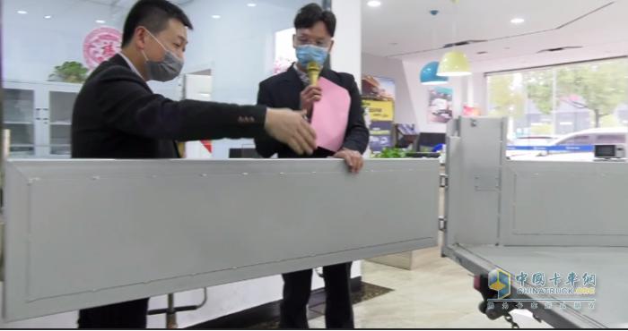 瑞沃营销公司销售副总经理王波先生现场演示福田小金刚的货箱后板侧开设计
