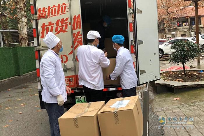 医院工作人员将盒饭从缔途EX上卸载下来