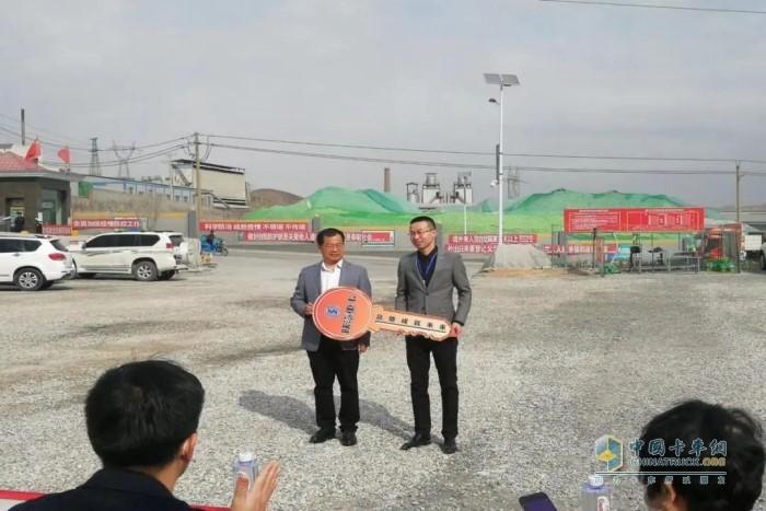 陕重汽销售公司副总经理王永锋向客户递交了象征着精诚合作、共创辉煌的金钥匙