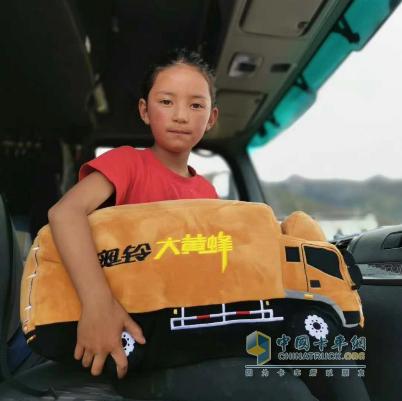 受助儿童坐在奥铃大黄蜂车里