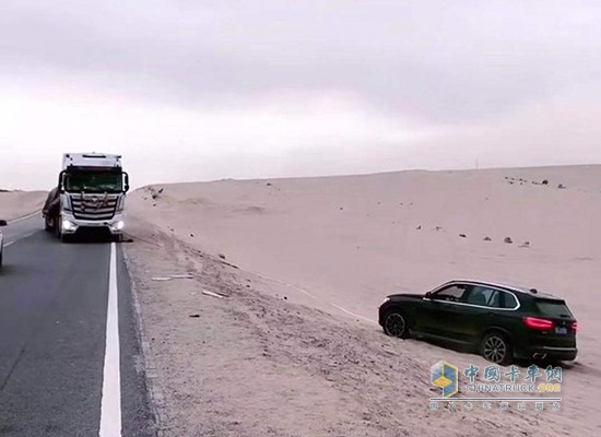 窦向永用卡车救陷入沙坑的轿车出来